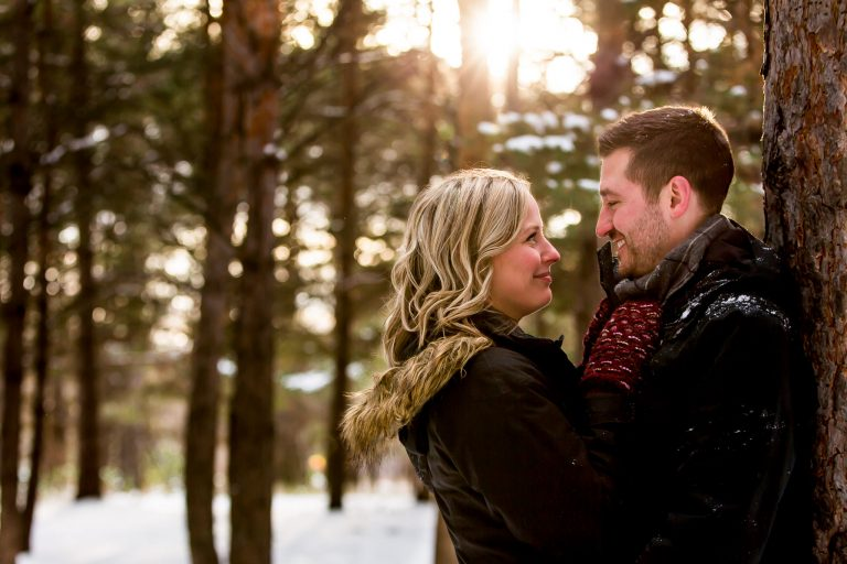 A couple standing in a forest getting their Winnipeg Engagement Photography photos