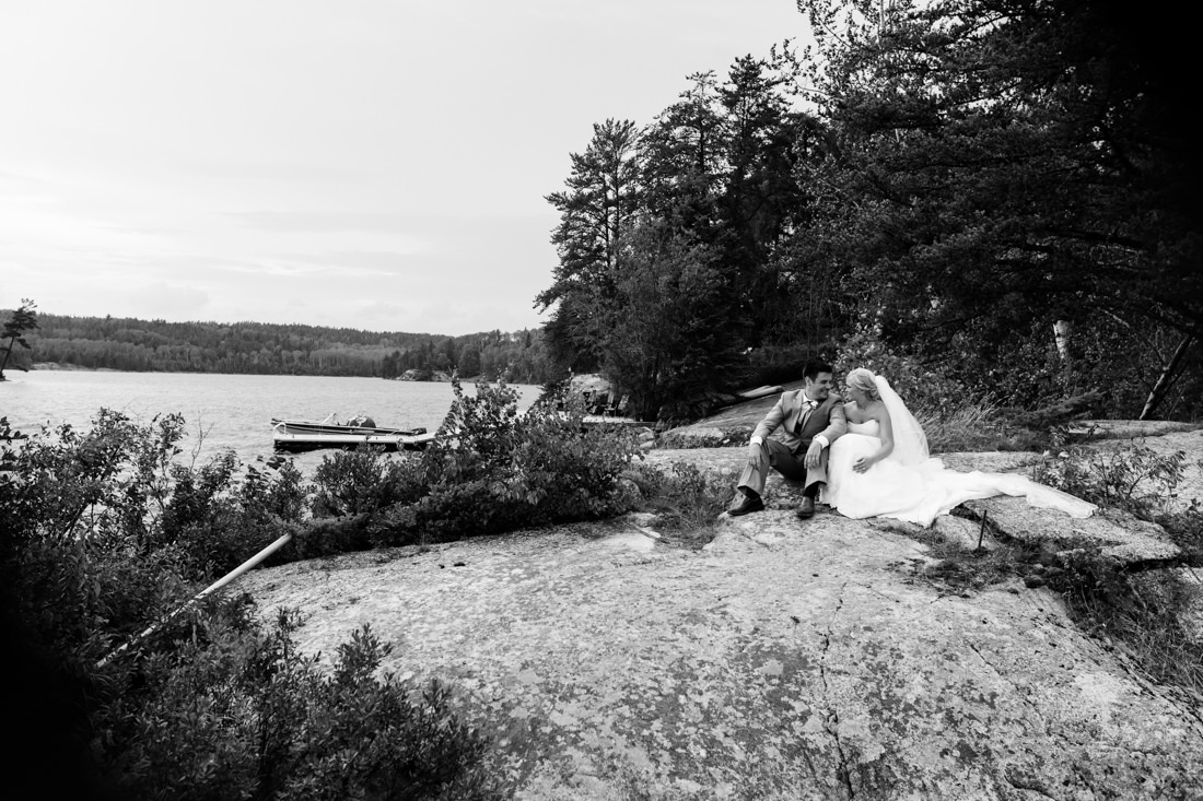 Couple sitting on the rocks, overlooking a lake